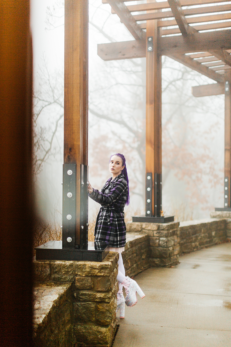 A beautiful young woman with purple hair poses for a Ault Park fashion photography session near Cincinnati, Ohio wearing a tweed jacket a light pink dress, white stockings and large rainbow heels while leaning against a wooden pillar as fog sets in