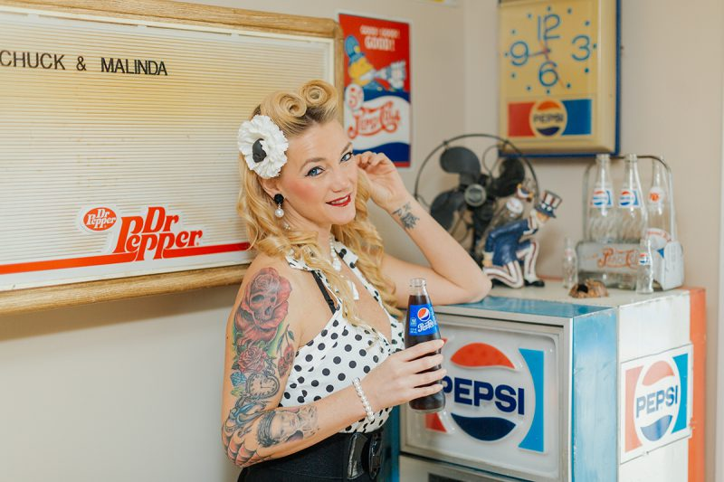 A beautiful blonde woman poses for a Cincinnati pin-up photography session in Dayton, Ohio wearing a polkadot blouse, a white flower in her hair and a black pencil skirt holding a Pepsi in front of a Pepsi refrigerator