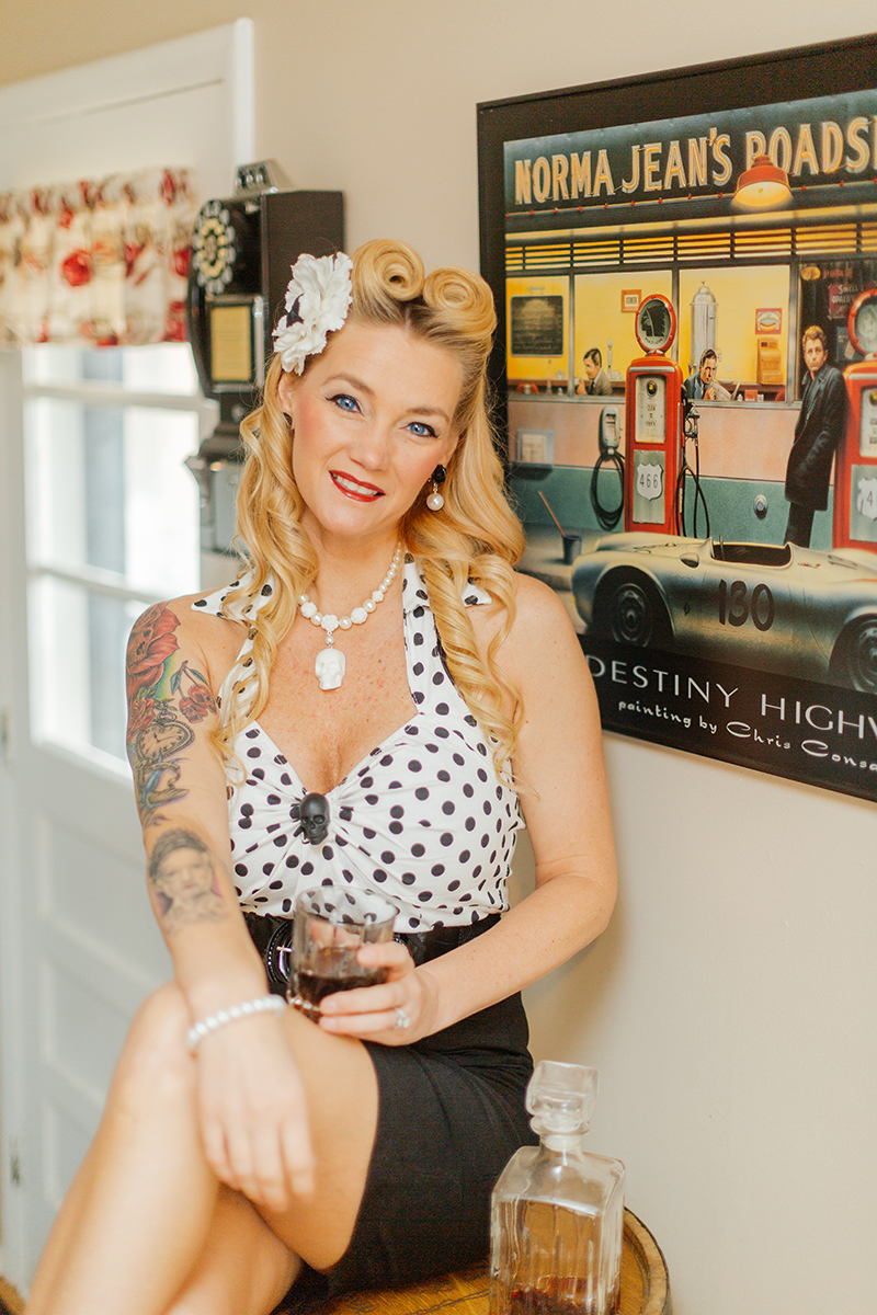 A beautiful blonde woman poses for a Cincinnati pin-up photography session in Dayton, Ohio wearing a polkadot blouse, a white flower in her hair and a black pencil skirt sitting on an oak barrel with whiskey in a glass