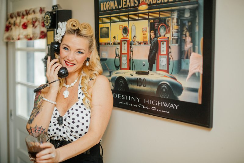 A beautiful blonde woman poses for a Cincinnati pin-up photography session in Dayton, Ohio wearing a polkadot blouse, a white flower in her hair and a black pencil skirt sitting on an oak barrel with whiskey in a glass while on the telephone