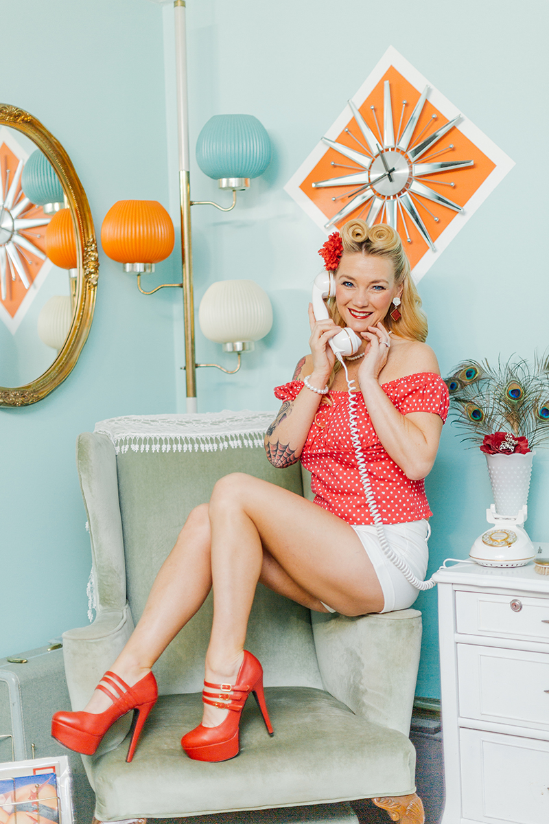 A beautiful blonde woman poses for a Cincinnati pin-up photography session in Dayton, Ohio wearing a pink blouse, white shorts and a pink flower in her hair sitting on the arm of a chair talking on the phone in a retro room