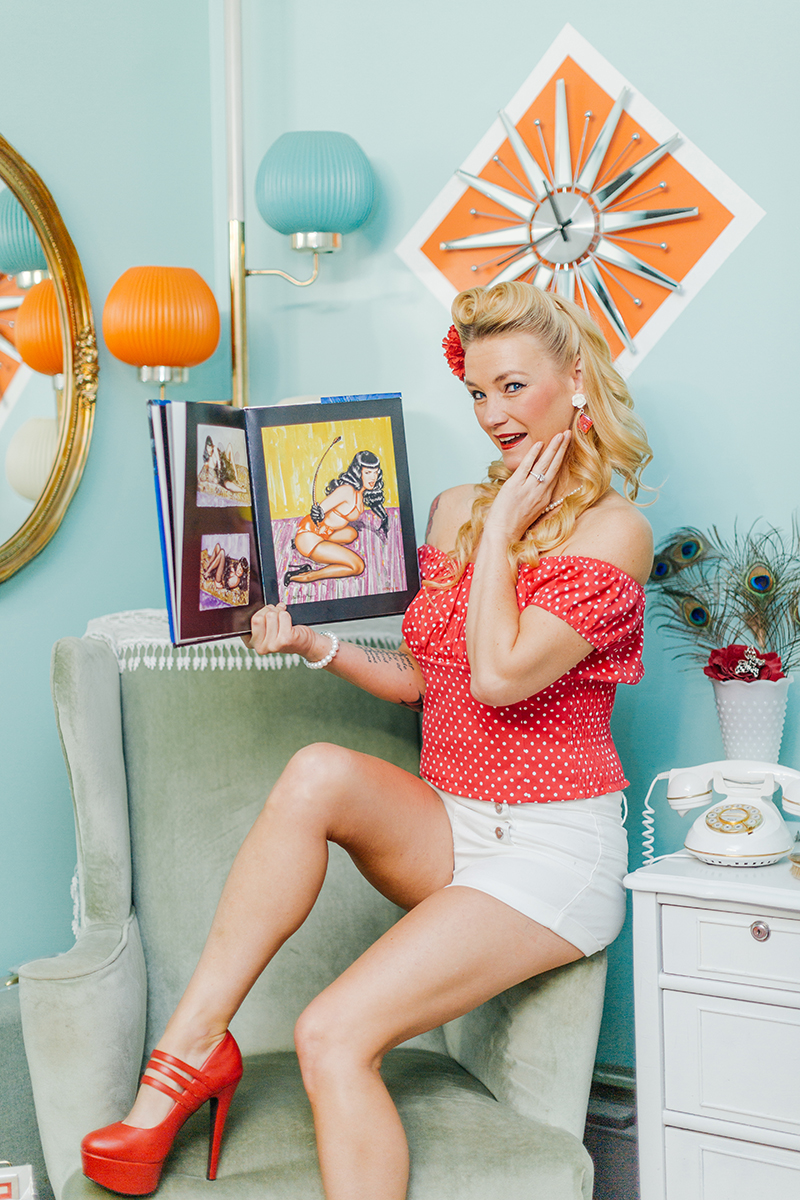 A beautiful blonde woman poses for a Cincinnati pin-up photography session in Dayton, Ohio wearing a pink blouse, white shorts and a pink flower in her hair sitting on the arm of a chair reading a Bettie Paige magazine in a retro room