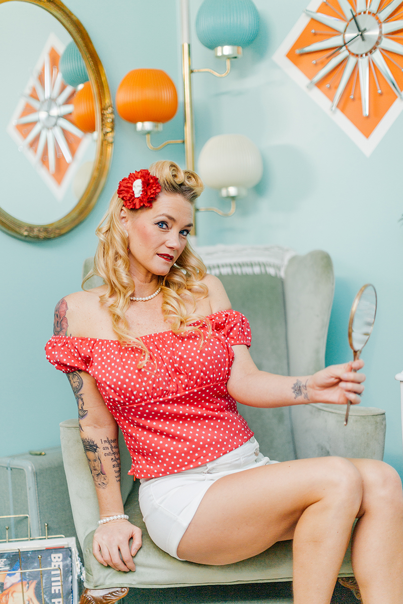 A beautiful blonde woman poses for a Cincinnati pin-up photography session in Dayton, Ohio wearing a pink blouse, white shorts and a pink flower in her hair sitting on the arm of a chair holding a hand mirror in a retro room