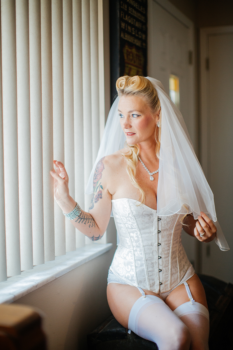 A beautiful blonde woman poses for a Cincinnati pin-up photography session in Dayton, Ohio wearing a white corset, white stockings, white underwear and a white garter with a white bridal veil in her hair sitting in front of a window