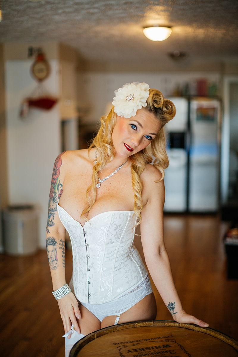 A beautiful blonde woman poses for a Cincinnati pin-up photography session in Dayton, Ohio wearing a white corset, white stockings, white underwear and a white garter with a white flower in her hair sitting on an oak barrel