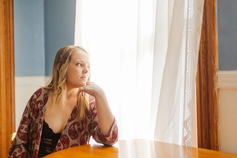 A beautiful young blonde woman poses for a Dayton in-home boudoir photography session in our home near Cincinnati, Ohio wearing a black lingerie body suit and a red robe while sitting at a table in front of a window