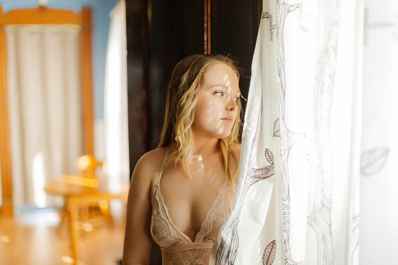 A beautiful young blonde woman poses for a Dayton in-home boudoir photography session in our home near Cincinnati, Ohio wearing a tan lingerie body suit standing in front of a window with curtains