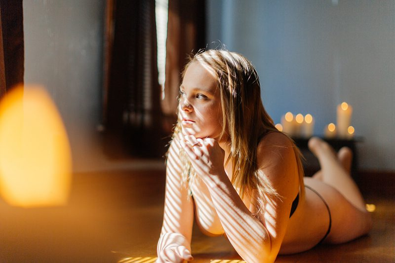 A beautiful young blonde woman poses for a Dayton in-home boudoir photography session in our home near Cincinnati, Ohio wearing a black bra and black underwear set laying on a wood floor near a window with candles all around her