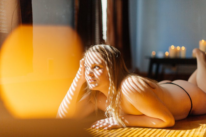 A beautiful young blonde woman poses topless for a Dayton in-home boudoir photography session in our home near Cincinnati, Ohio wearing black underwear laying on a wood floor near a window with candles all around her