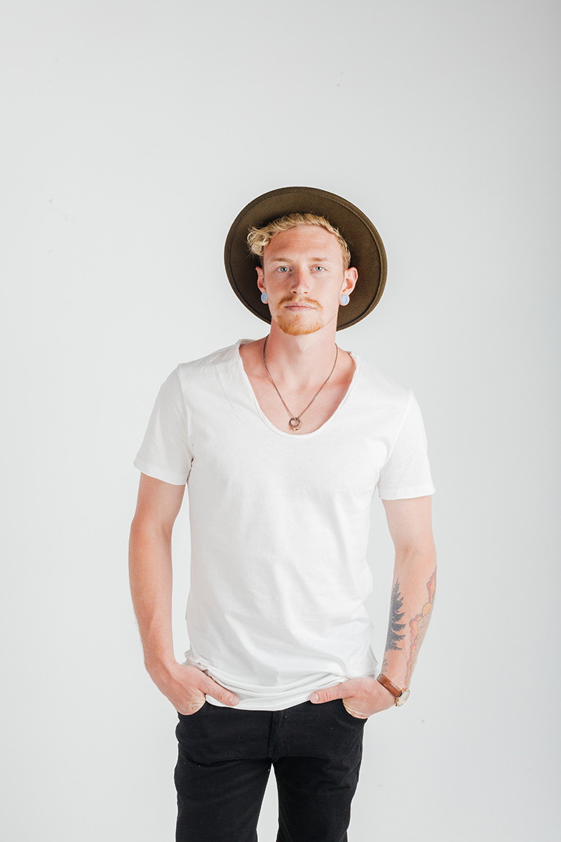 A handsome young blonde male model poses for a RAW Photographic Studio fashion photography session in Denver, Colorado wearing a tan bohemian hat, a white shirt and black pants