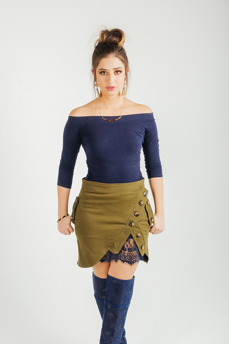 A beautiful young brunette female model poses for a RAW Photographic Studio fashion photography session in Denver, Colorado wearing a blue shirt with an olive skirt and black boots