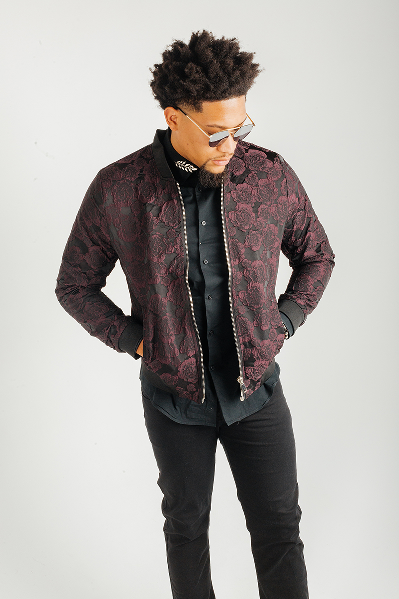 A handsome young brunette African American male model poses for a RAW Photographic Studio fashion photography session in Denver, Colorado wearing a black button up shirt, black pants and a red rose jacket