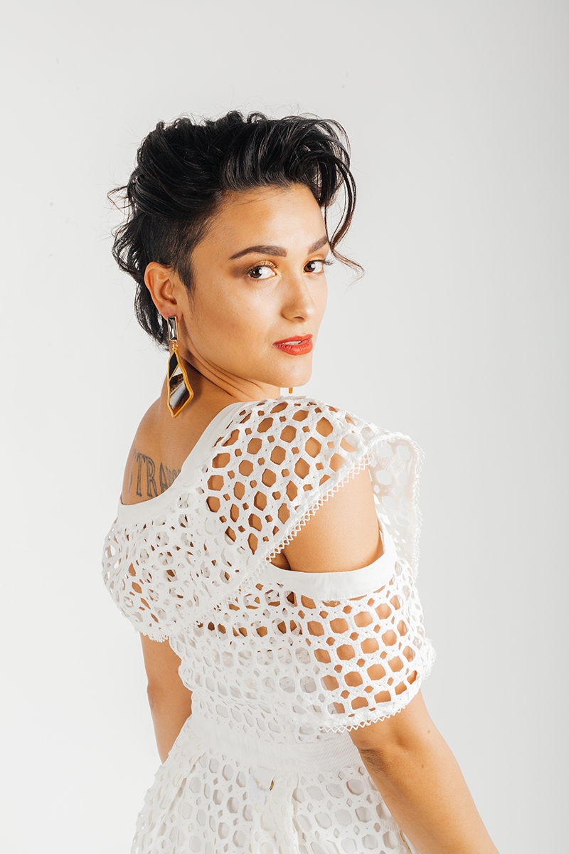 A beautiful young brunette hispanic female model poses for a RAW Photographic Studio fashion photography session in Denver, Colorado wearing a white lace dress
