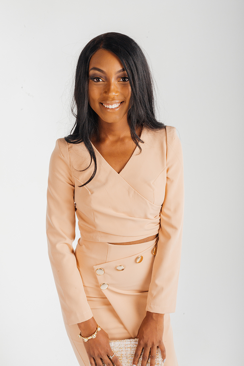 A beautiful young brunette African American female model poses for a RAW Photographic Studio fashion photography session in Denver, Colorado wearing a tan long sleeve shirt and skirt holding a white purse