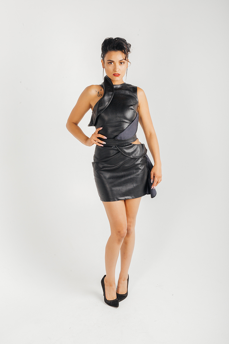 A beautiful young brunette hispanic female model poses for a RAW Photographic Studio fashion photography session in Denver, Colorado wearing a black leather dress