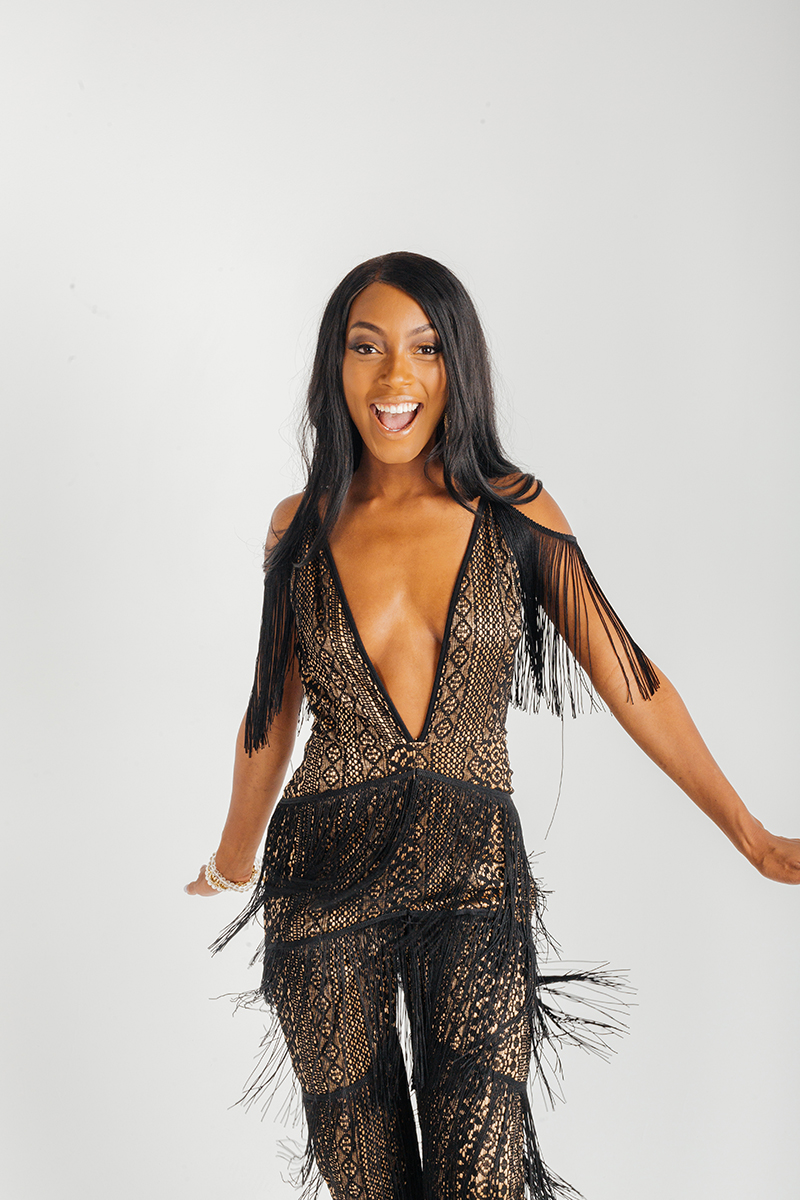 A beautiful young brunette African American female model poses for a RAW Photographic Studio fashion photography session in Denver, Colorado wearing a black fringe pant suit