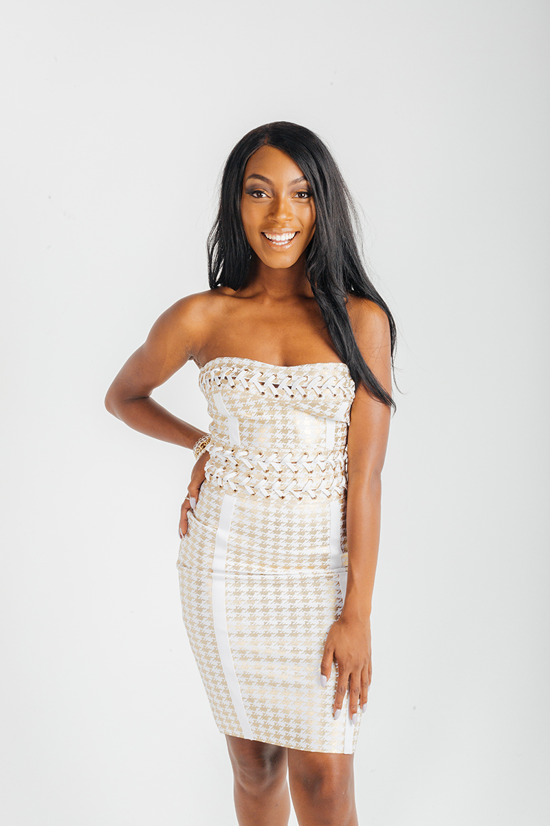 A beautiful young brunette African American female model poses for a RAW Photographic Studio fashion photography session in Denver, Colorado wearing a white lace dress