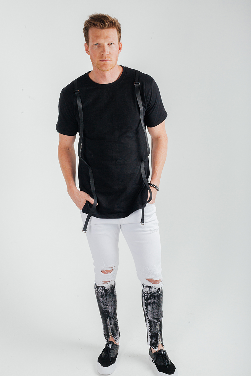 A handsome young blonde male model poses for a RAW Photographic Studio fashion photography session in Denver, Colorado wearing a black shirt with black straps and white pants that fade into black at the bottom