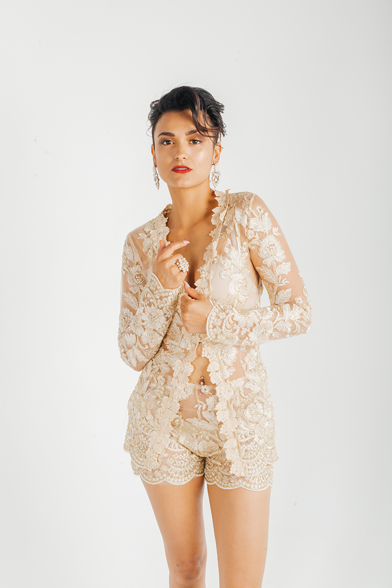 A beautiful young brunette hispanic female model poses for a RAW Photographic Studio fashion photography session in Denver, Colorado wearing a beige lace jacket and matching shorts