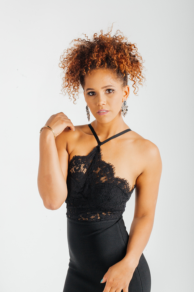 A beautiful young brunette African American female model poses for a RAW Photographic Studio fashion photography session in Denver, Colorado wearing a black strap dress
