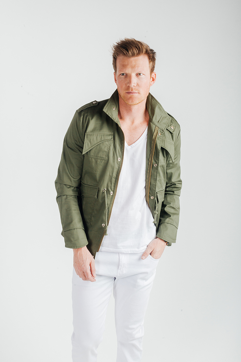 A handsome young blonde male model poses for a RAW Photographic Studio fashion photography session in Denver, Colorado wearing a white shirt and white pants and a green jacket