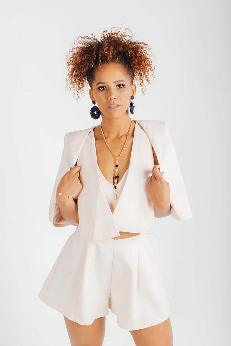 A beautiful young brunette African American female model poses for a RAW Photographic Studio fashion photography session in Denver, Colorado wearing a beige jacket, shirt and shorts