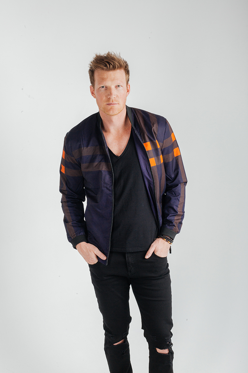 A handsome young blonde male model poses for a RAW Photographic Studio fashion photography session in Denver, Colorado wearing a black shirt, black pants and a blue jacket with an orange stripe