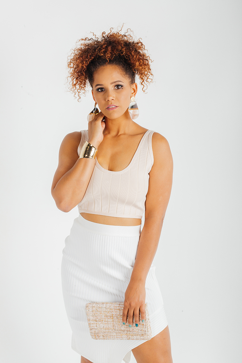 A beautiful young brunette African American female model poses for a RAW Photographic Studio fashion photography session in Denver, Colorado wearing a beige shirt and a white skirt