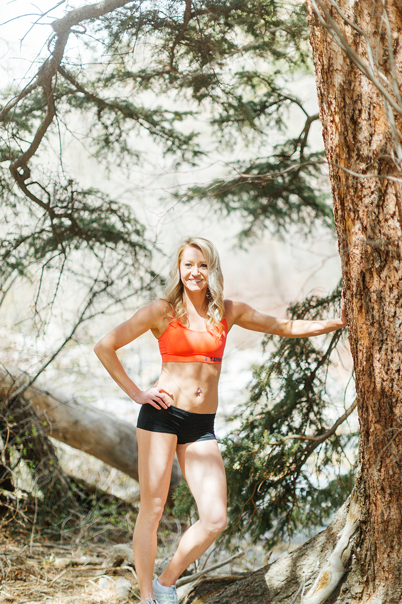 A beautiful and athletic blonde woman poses for a Grizzly Creek fitness photography session near Glenwood Springs, Colorado wearing an orange sports bra and black workout shorts leaning on a tree next to a creek
