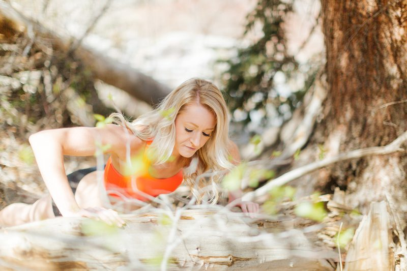 A beautiful and athletic blonde woman poses for a Grizzly Creek fitness photography session near Glenwood Springs, Colorado wearing an orange sports bra and black workout shorts doing a pushup next to a tree