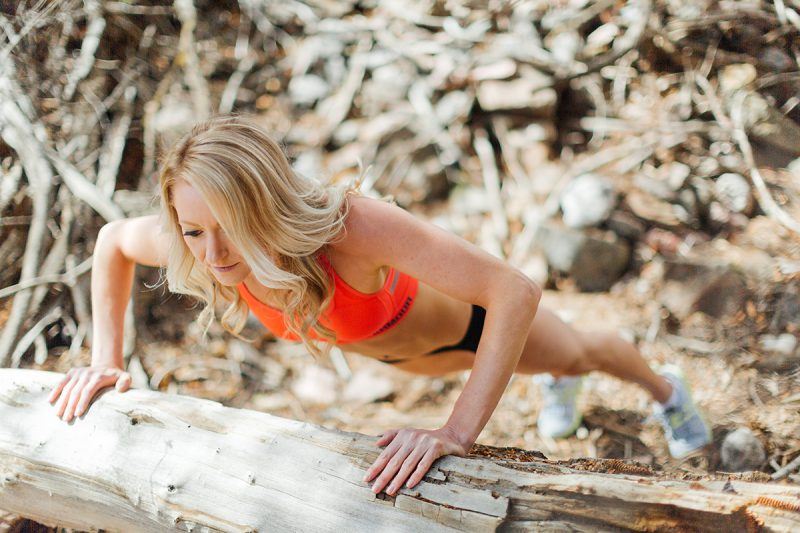 A beautiful and athletic blonde woman poses for a Grizzly Creek fitness photography session near Glenwood Springs, Colorado wearing an orange sports bra and black workout shorts doing a pushup n a fallen tree