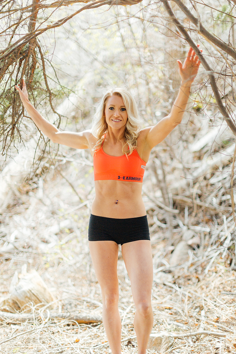 A beautiful and athletic blonde woman poses for a Grizzly Creek fitness photography session near Glenwood Springs, Colorado wearing an orange sports bra and black workout shorts holding on to branches of a tree