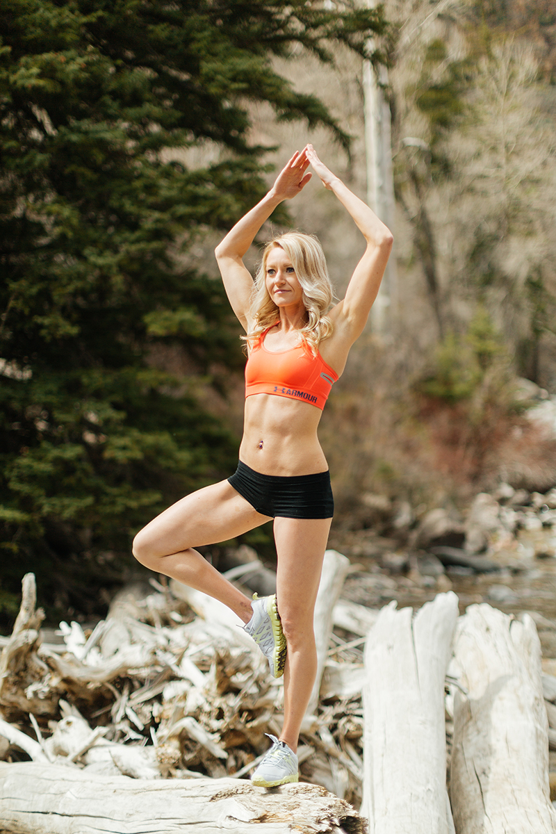 A beautiful and athletic blonde woman poses for a Grizzly Creek fitness photography session near Glenwood Springs, Colorado wearing an orange sports bra and black workout shorts holding a yoga pose on rocks in the middle of a creek