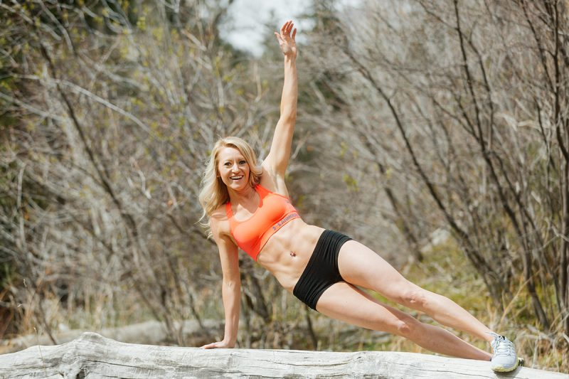 A beautiful and athletic blonde woman poses for a Grizzly Creek fitness photography session near Glenwood Springs, Colorado wearing an orange sports bra and black workout shorts holding a workout pose on a fallen tree in a field next to a creek