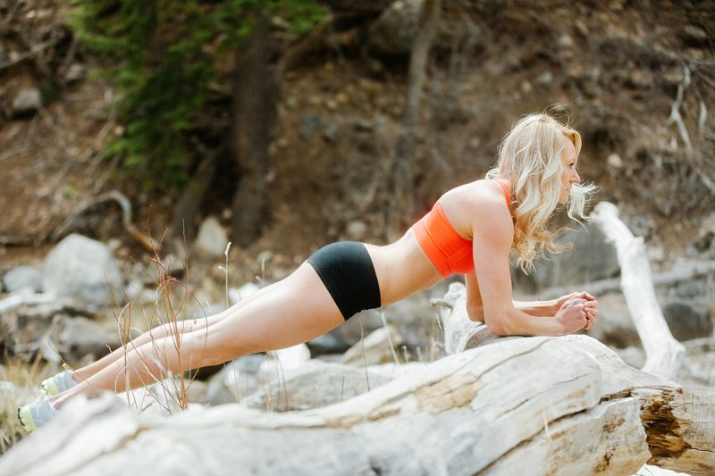 A beautiful and athletic blonde woman poses for a Grizzly Creek fitness photography session near Glenwood Springs, Colorado wearing an orange sports bra and black workout shorts holding a plank on a fallen tree in a field next to a creek
