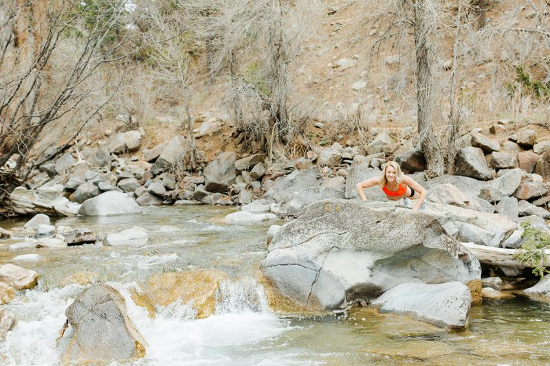 A beautiful and athletic blonde woman poses for a Grizzly Creek fitness photography session near Glenwood Springs, Colorado wearing an orange sports bra and black workout shorts doing pushups on a rock in the middle of a creek
