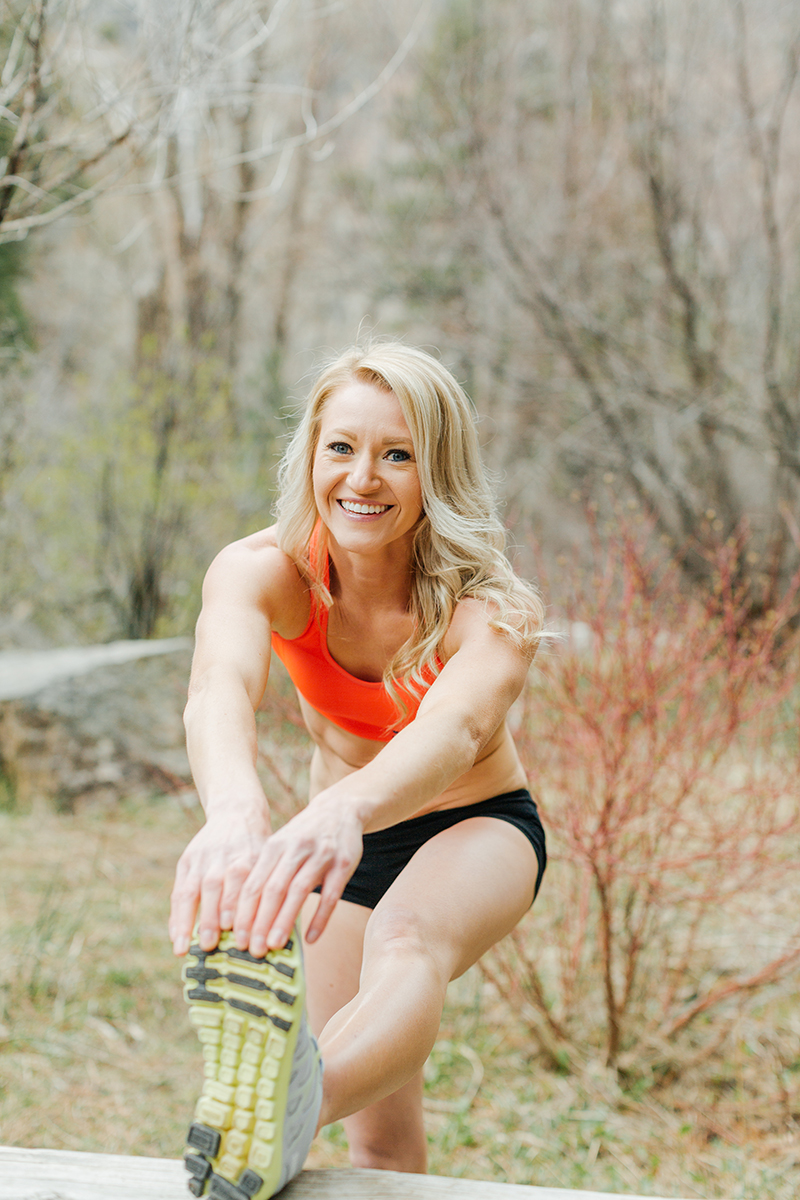A beautiful and athletic blonde woman poses for a Grizzly Creek fitness photography session near Glenwood Springs, Colorado wearing an orange sports bra and black workout shorts holding a stretch on a picnic table in a field