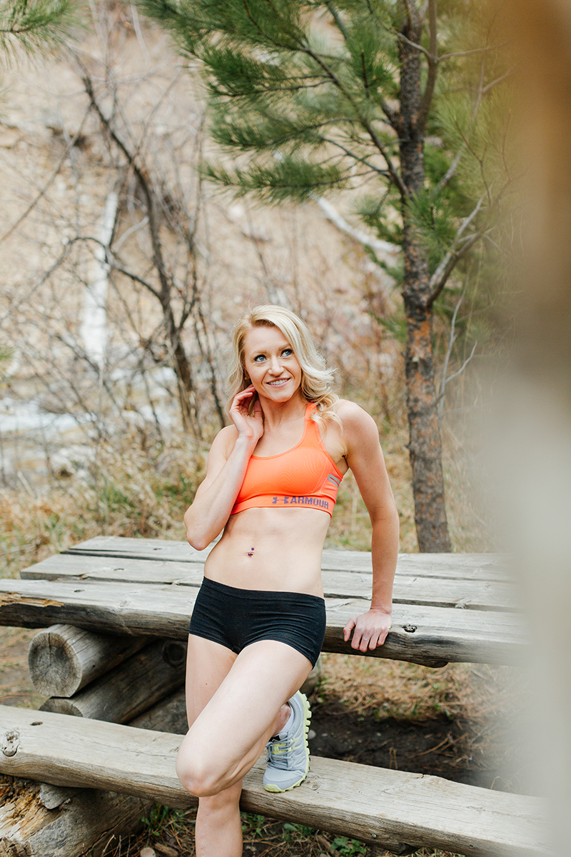 A beautiful and athletic blonde woman poses for a Grizzly Creek fitness photography session near Glenwood Springs, Colorado wearing an orange sports bra and black workout shorts leaning on a picnic table in a field
