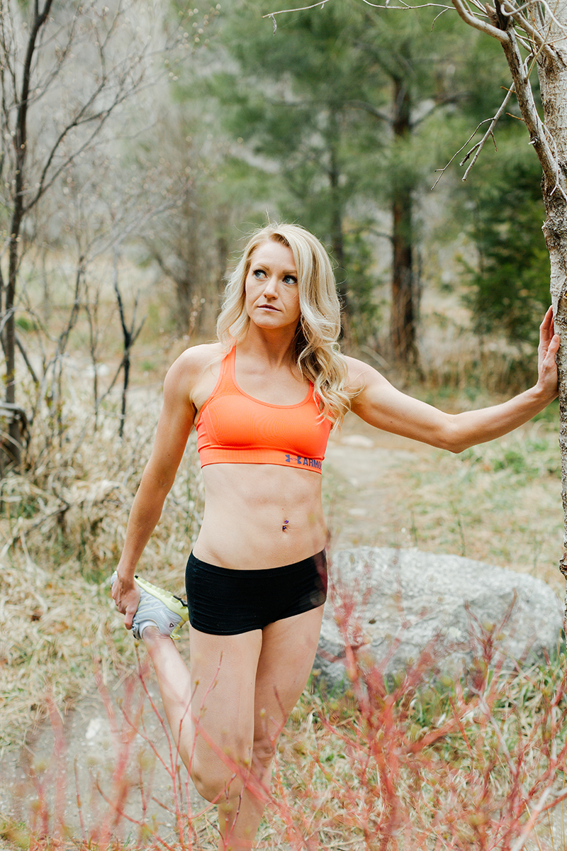 A beautiful and athletic blonde woman poses for a Grizzly Creek fitness photography session near Glenwood Springs, Colorado wearing an orange sports bra and black workout shorts leaning on a tree while stretching in a field