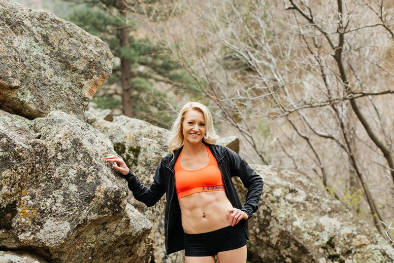 A beautiful and athletic blonde woman poses for a Grizzly Creek fitness photography session near Glenwood Springs, Colorado wearing an orange sports bra, a black workout jacket and black workout shorts leaning on a boulder in a field