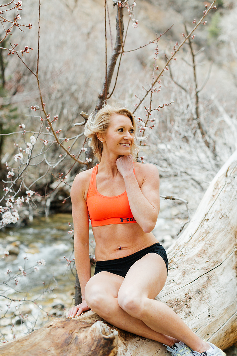 A beautiful and athletic blonde woman poses for a Grizzly Creek fitness photography session near Glenwood Springs, Colorado wearing an orange sports bra and black workout shorts sitting on a fallen log with cherry blossoms around her in front of the creek
