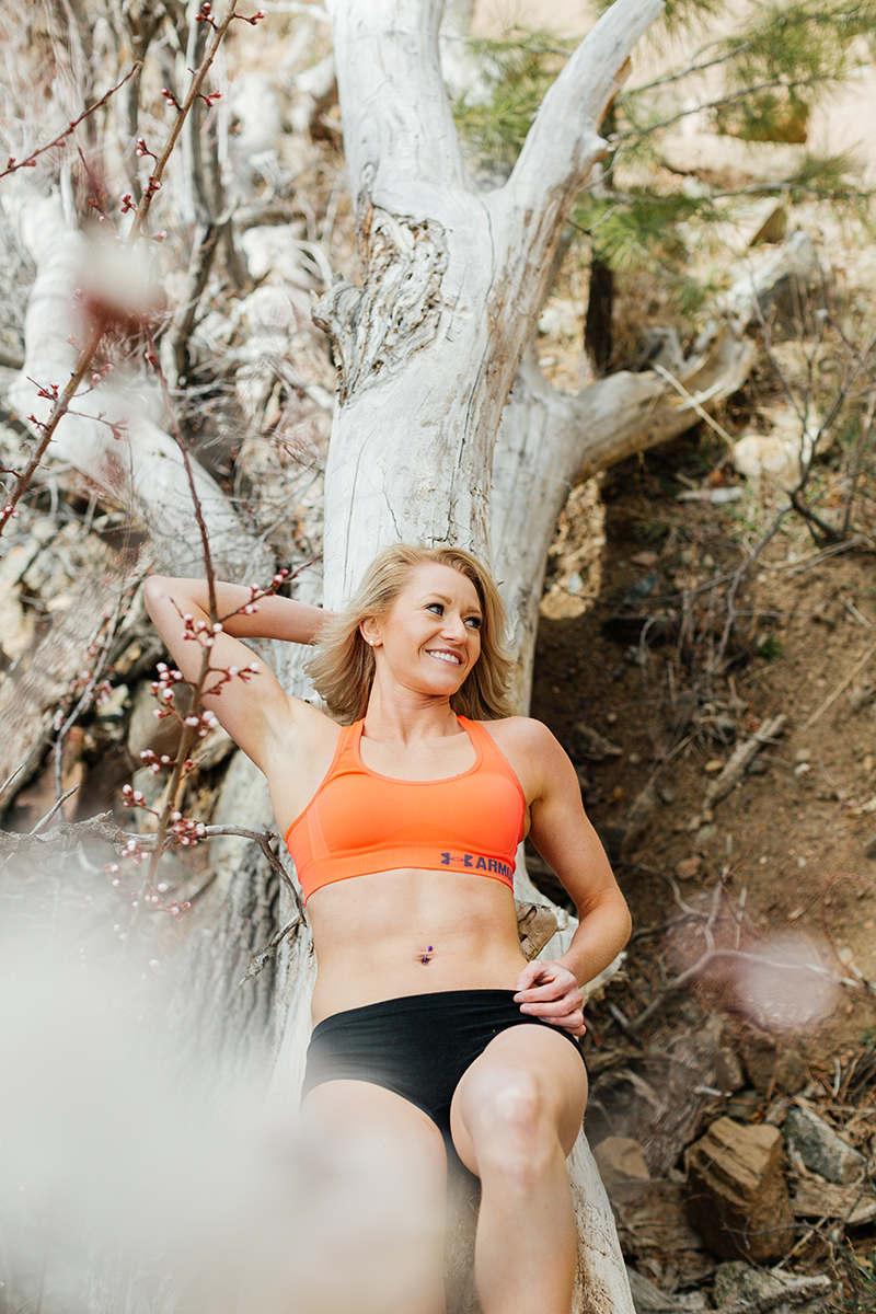 A beautiful and athletic blonde woman poses for a Grizzly Creek fitness photography session near Glenwood Springs, Colorado wearing an orange sports bra and black workout shorts laying on a fallen log with cherry blossoms around her next to the creek