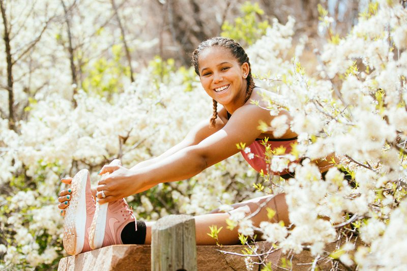 A beautiful young African American woman posing for a Red Rocks Amphitheater fitness session near Denver, Colorado wearing black workout shorts with a black and pink sports bra stretching on a trail surrounded by white flower blossoms