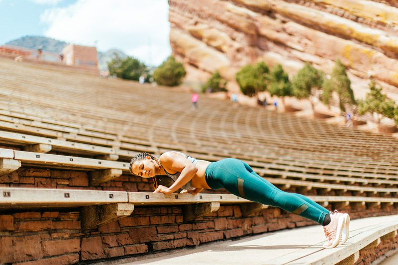 A beautiful young African American woman posing for a Red Rocks Amphitheater fitness session near Denver, Colorado wearing green leggings with a gray and black sports bra doing a plank on the wood steps