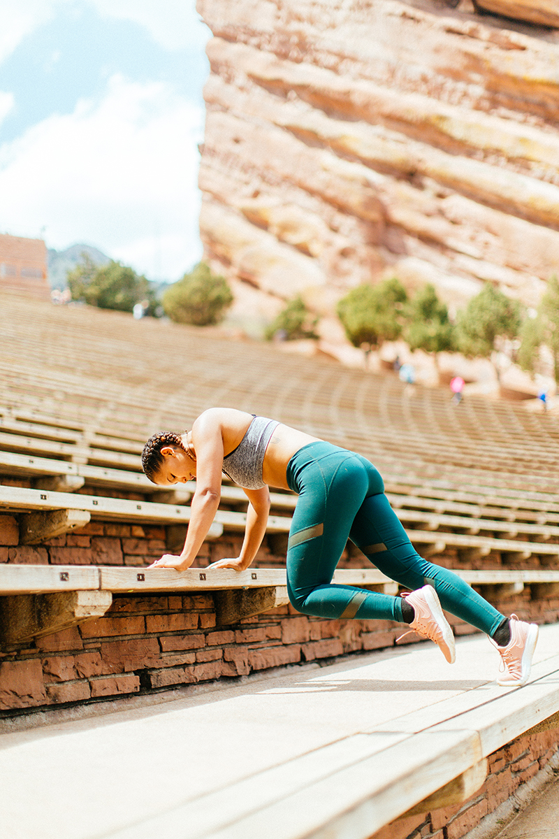 A beautiful young African American woman posing for a Red Rocks Amphitheater fitness session near Denver, Colorado wearing green leggings with a gray and black sports bra doing a workout on the wood steps