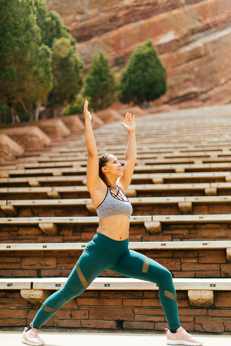 A beautiful young African American woman posing for a Red Rocks Amphitheater fitness session near Denver, Colorado wearing green leggings with a gray and black sports bra doing a yoga pose on the wood steps