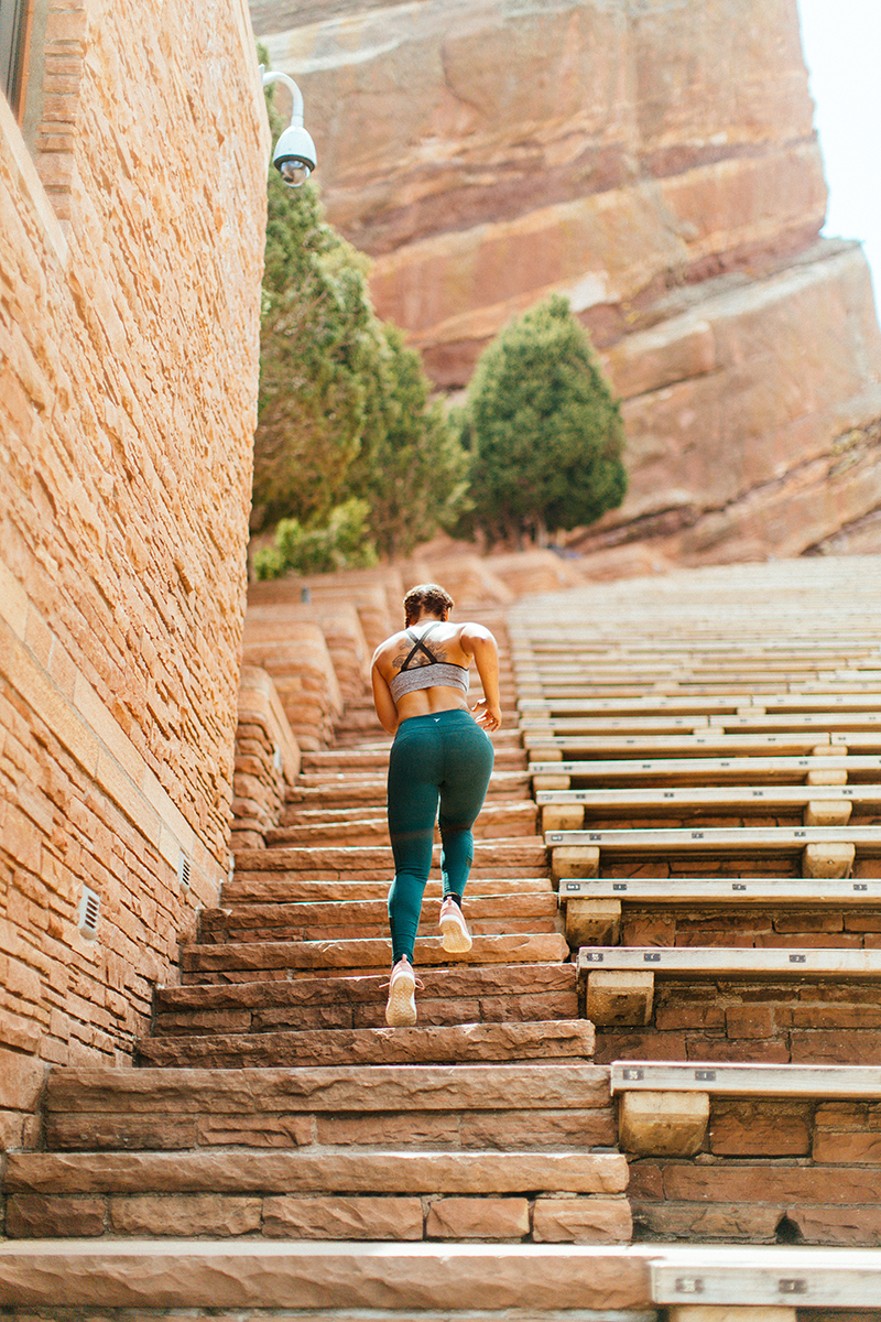 A beautiful young African American woman posing for a Red Rocks Amphitheater fitness session near Denver, Colorado wearing green leggings with a gray and black sports bra running up the stone steps