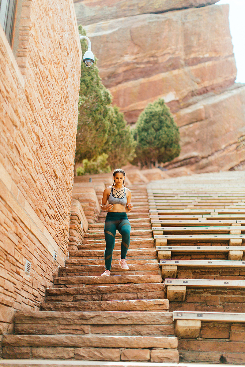 A beautiful young African American woman posing for a Red Rocks Amphitheater fitness session near Denver, Colorado wearing green leggings with a gray and black sports bra running down the stone steps