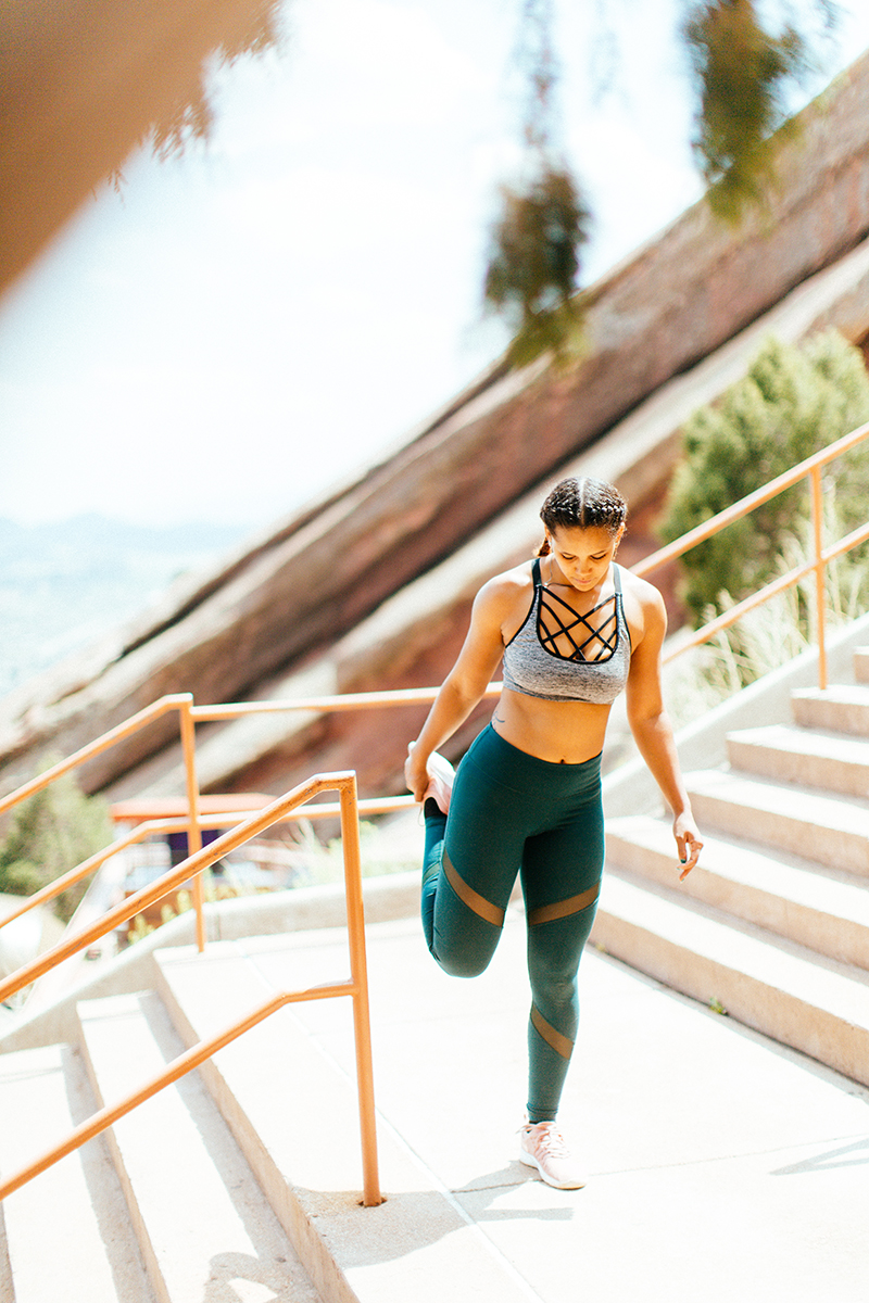 A beautiful young African American woman posing for a Red Rocks Amphitheater fitness session near Denver, Colorado wearing green leggings with a gray and black sports bra stretching on the wood steps