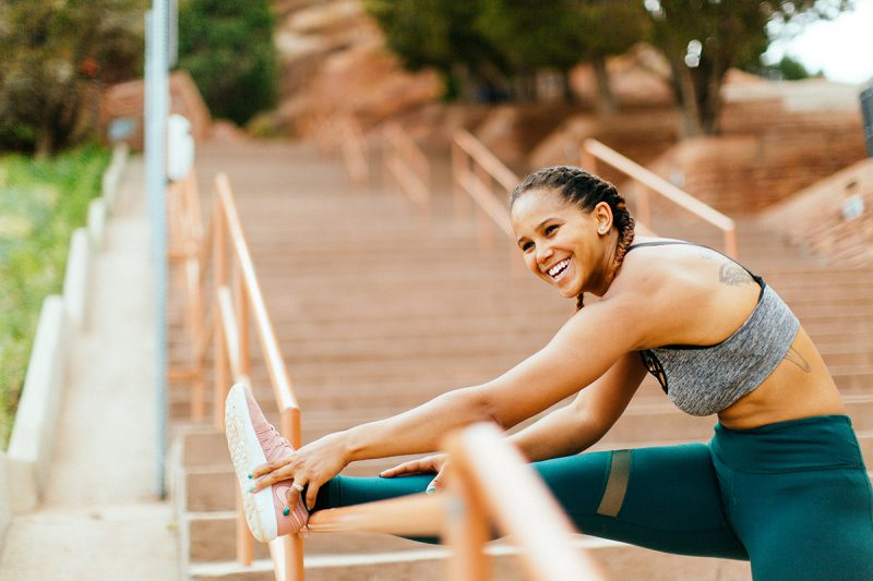 A beautiful young African American woman posing for a Red Rocks Amphitheater fitness session near Denver, Colorado wearing green leggings with a gray and black sports bra stretching her leg on railing on the wood steps